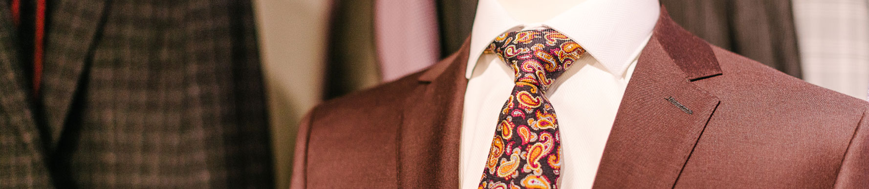 A display of a burgundy jacket over a white dress shirt. There is a colorful tie and white pocket square