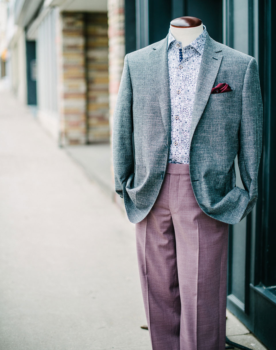 A display outside of the Taylor and Co store. A grey sport coat over a fun dress shirt, with purple pants.