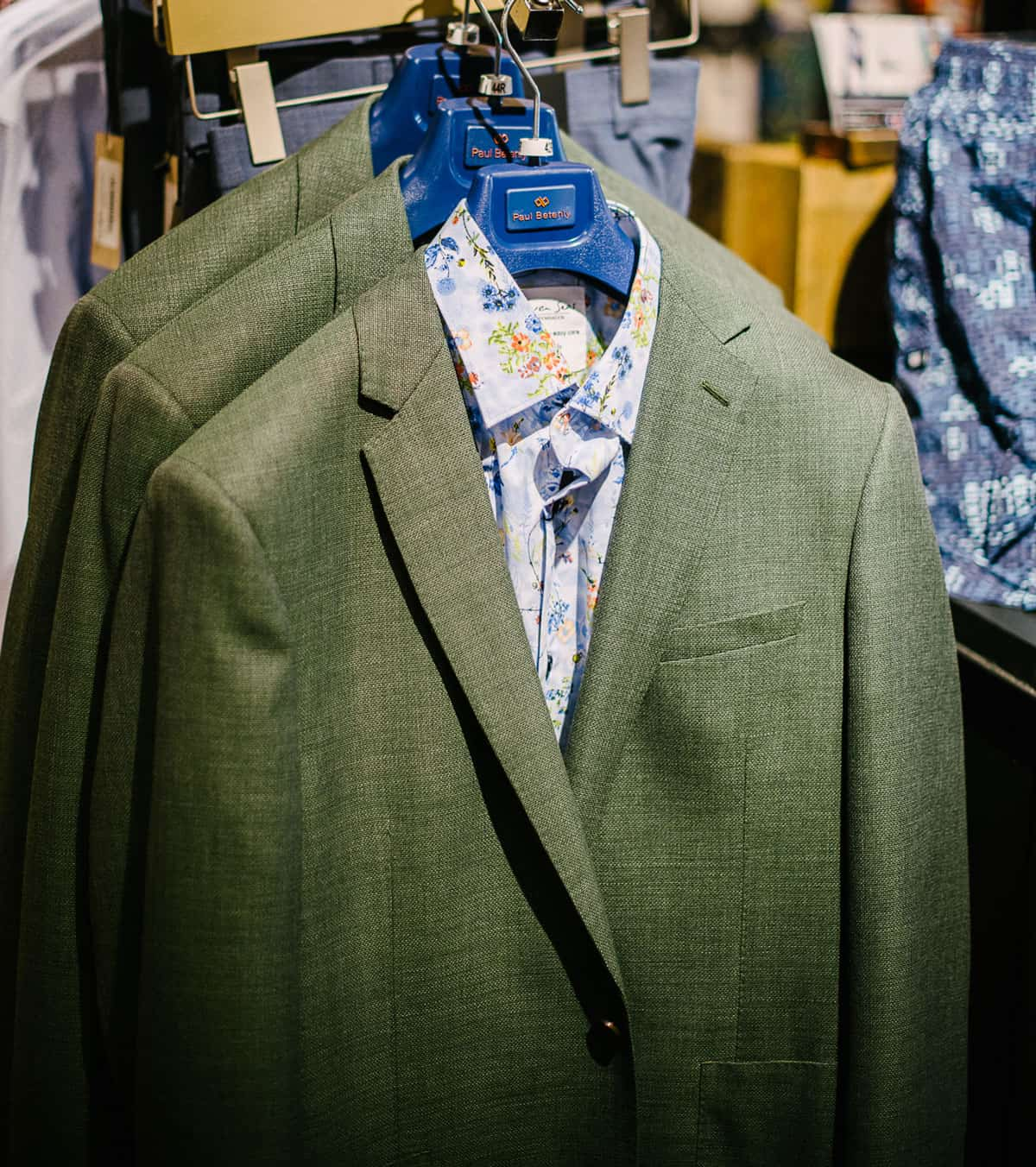 A green sport coat over a dress shirt on a rack of items in-store.
