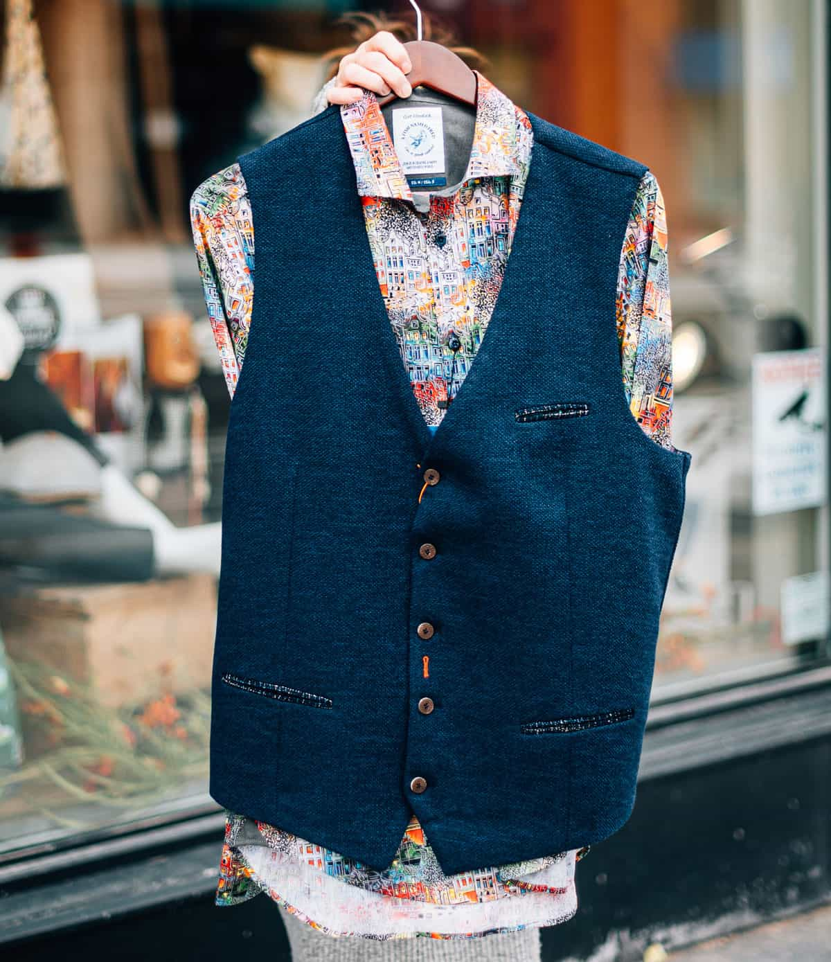A blue vest over top on a colourful shirt from A Fish Named Fred.