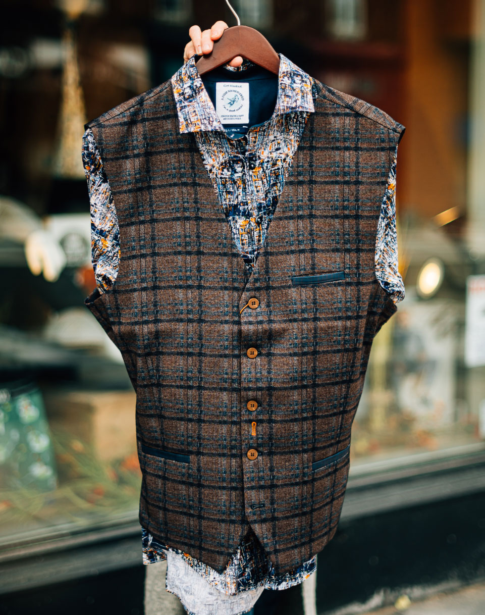 A brown and blue plaid men's vest over top a colourful dress shirt on a coat hanger