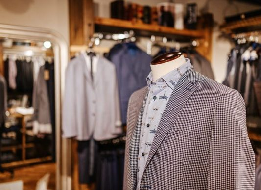 A mannequin with a brown blazer and a colourful dress shirt.